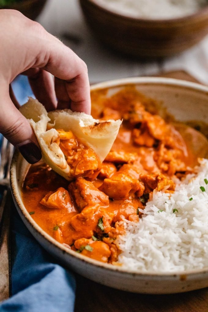 Scooping chicken tikka masala with naan bread