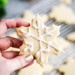 holding decorated sugar cookie snowflake
