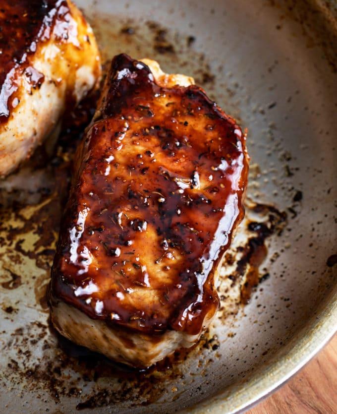 Baked pork chops with bourbon glaze in skillet