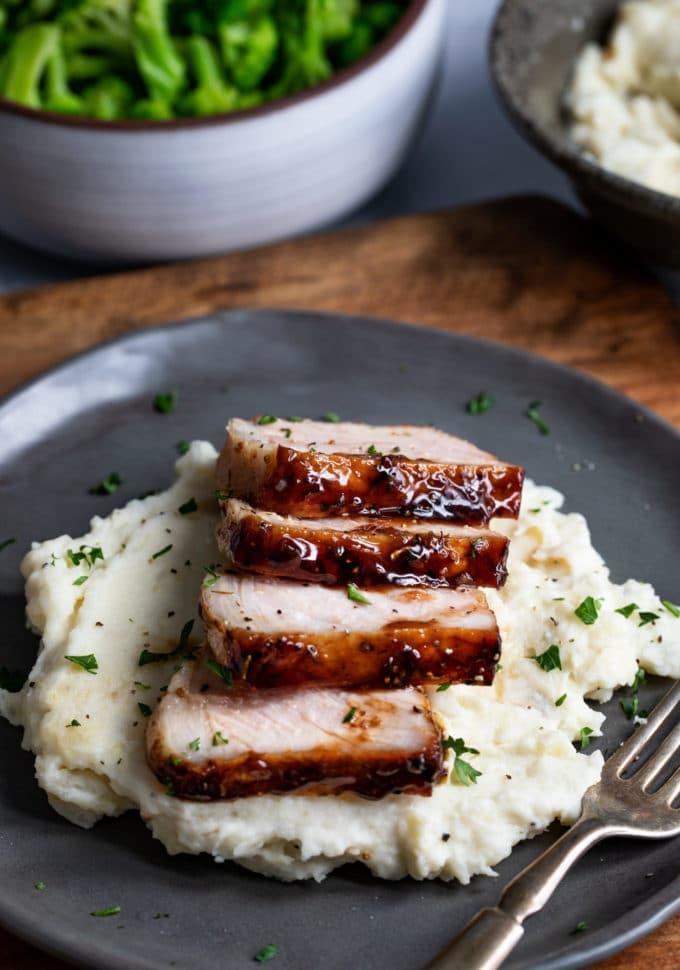 Sliced baked pork chops over mashed potatoes