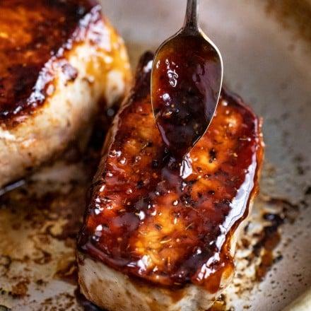 Spooning bourbon glaze over baked pork chops