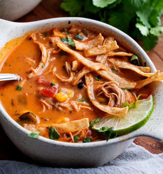 White bowl of tortilla soup with garnishes