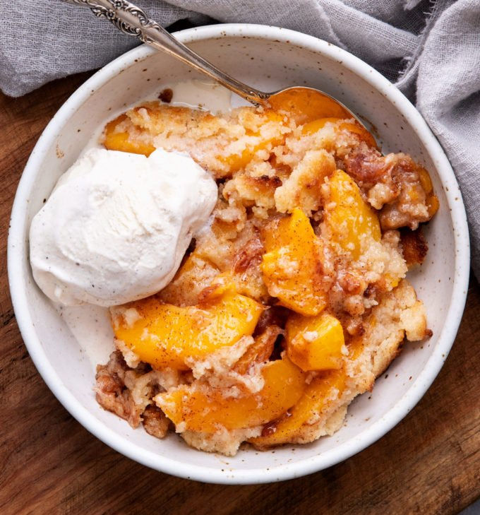 View of cobbler in white bowl with vanilla ice cream