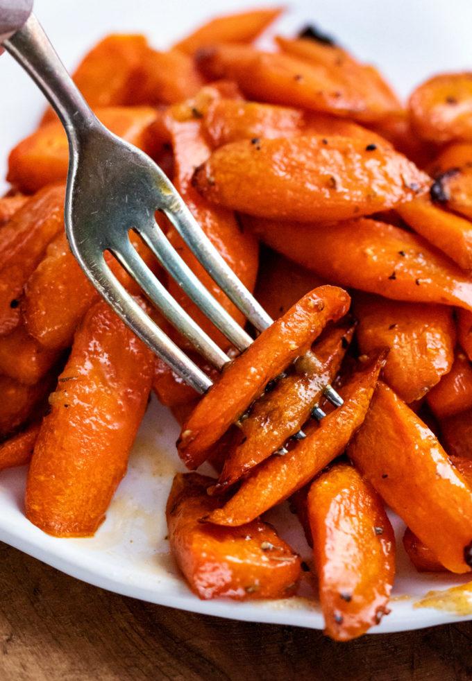 fork piercing 3 carrots on plate