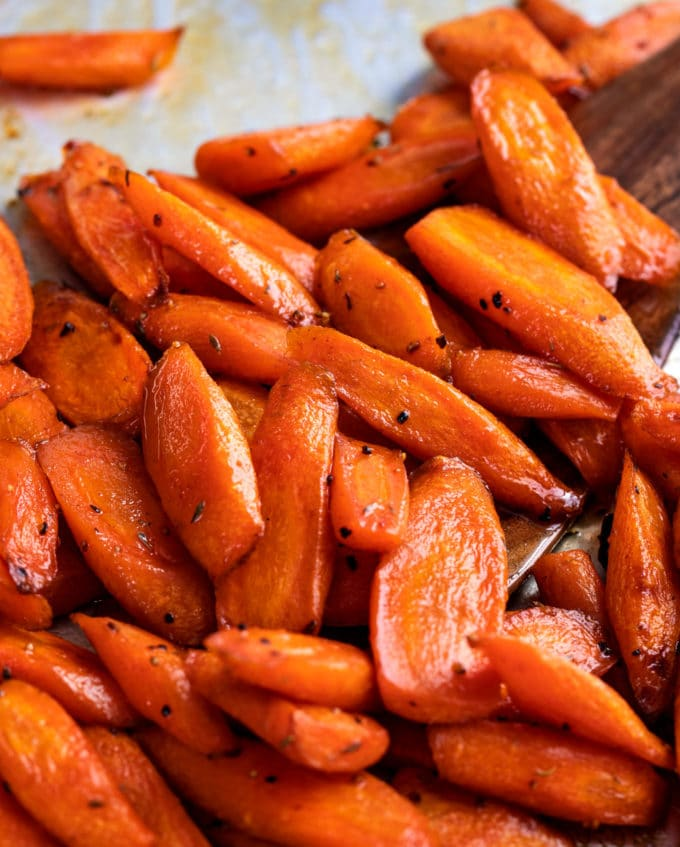 carrots on baking sheet with wooden spatula