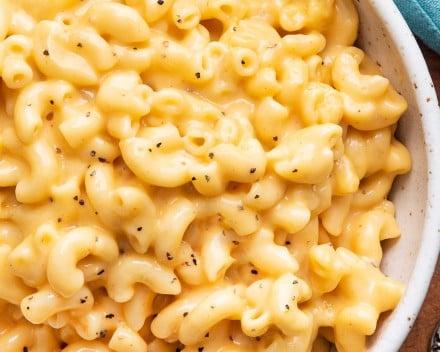 Overhead view of cheesy macaroni in white bowl