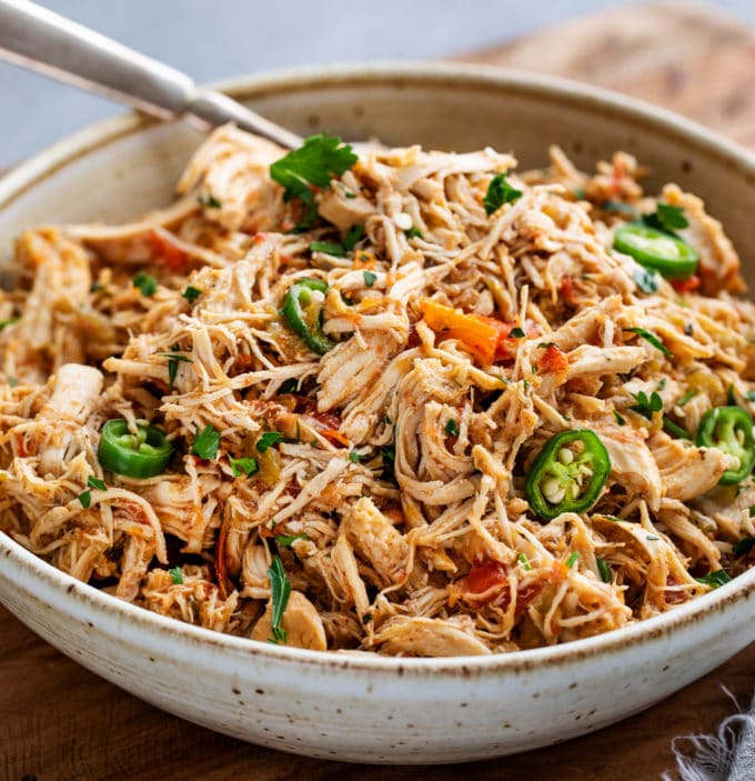 Tender shredded chicken, smothered in the most mouthwatering Mexican sauce made from salsa, green chiles, tomatoes and plenty of bold spices!  Perfect pantry meal, and can be used for so many things (tacos, enchiladas, etc). #chicken #mexican #salsa #shredded #instantpot #pressurecooker #slowcooker #crockpot #cincodemayo #taconight