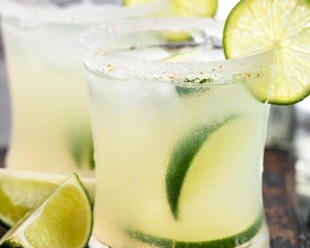Fresh margaritas with lime wedges and salt rims