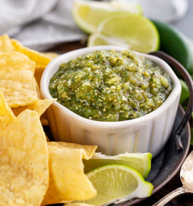 roasted tomatillo salsa in white bowl with chips around it