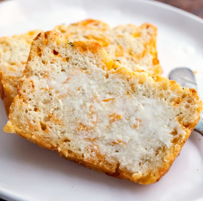 Beer bread with butter on white plate with butter knife