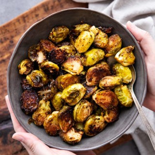 holding a bowl of roasted brussels sprouts