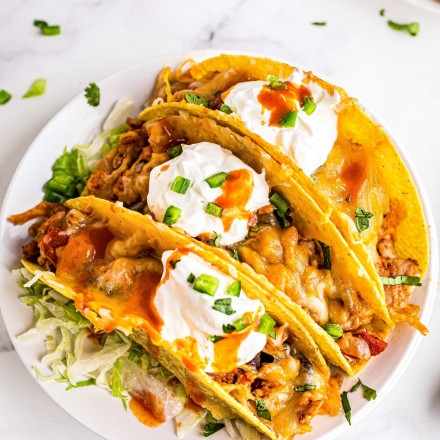 three chicken tacos on white plate