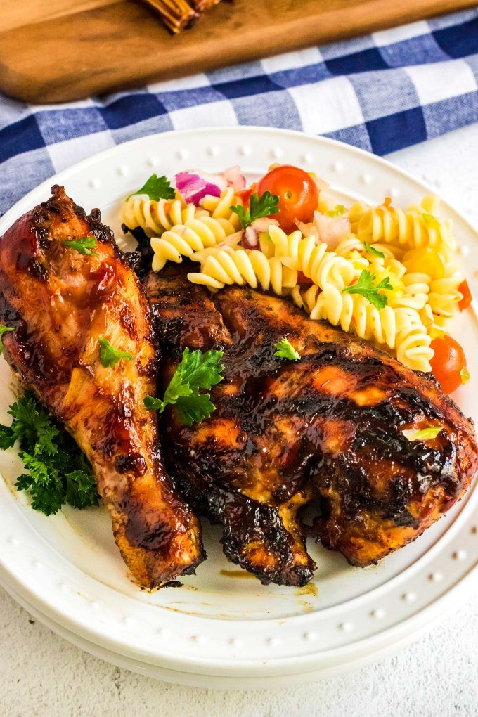 bbq chicken on white plate with pasta salad
