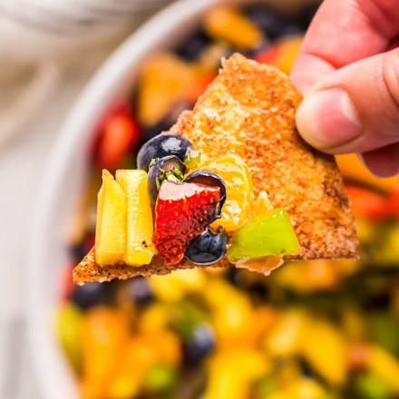 holding a chip with fruit salsa on it