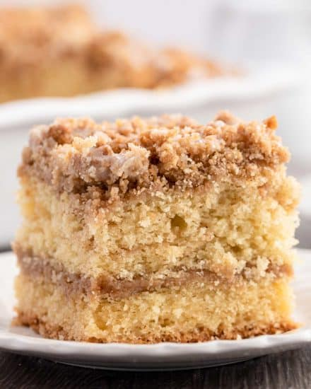 My favorite Sour Cream Coffee Cake is ultra moist and buttery, with a cinnamon streusel layer in the middle and on top, and drizzled with a sweet glaze. #coffeecake #crumbcake #sourcream #baking #breakfast #dessert #cinnamon #streusel #brunch