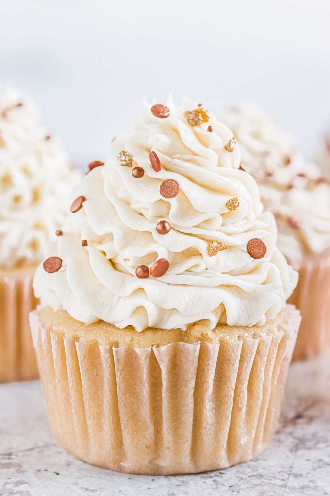 closeup photo of vanilla cupcake with swirled buttercream and sprinkles