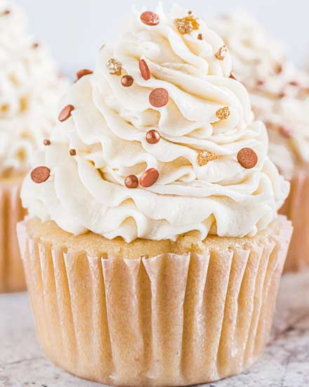 These Bourbon Vanilla Cupcakes are perfectly moist, and completely irresistible!  Light and fluffy cupcakes are spiked with bourbon and swirled with creamy vanilla buttercream for the ultimate dessert. #cupcakes #baking #dessert #vanilla #bourbon #fallbaking #dessertrecipe