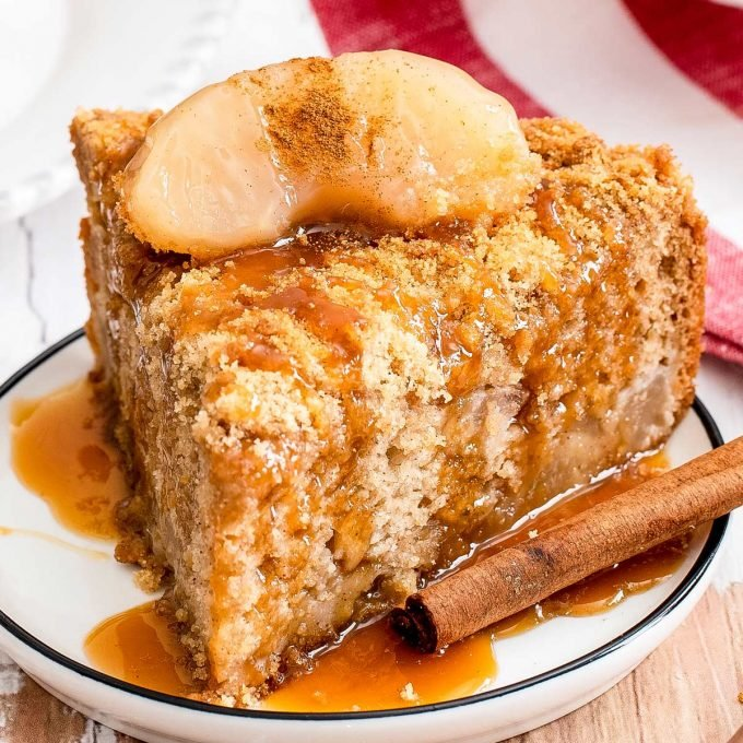 slice of apple cake on plate with caramel sauce