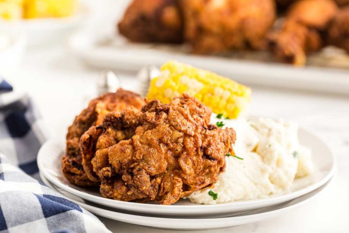 fried chicken on plate with mashed potatoes and corn