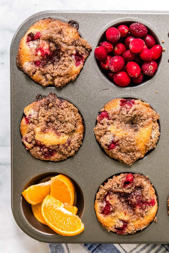 cranberry orange muffins in muffin pan with fresh fruit
