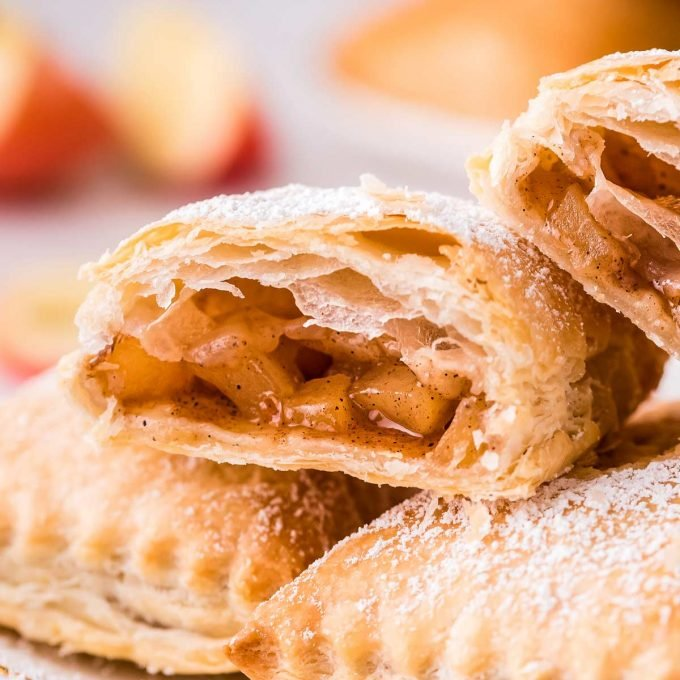 apple turnovers stacked on plate, one cut open