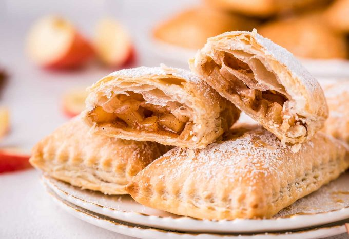 These homemade Apple Turnovers are filled with a spiced apple filling and baked in flaky, buttery puff pastry dough. Dust with powdered sugar or drizzle with glaze, and you have a breakfast that tastes like apple pie! #turnover #apple #applepie #applecinnamon #pastry #breakfast #dessert #baking
