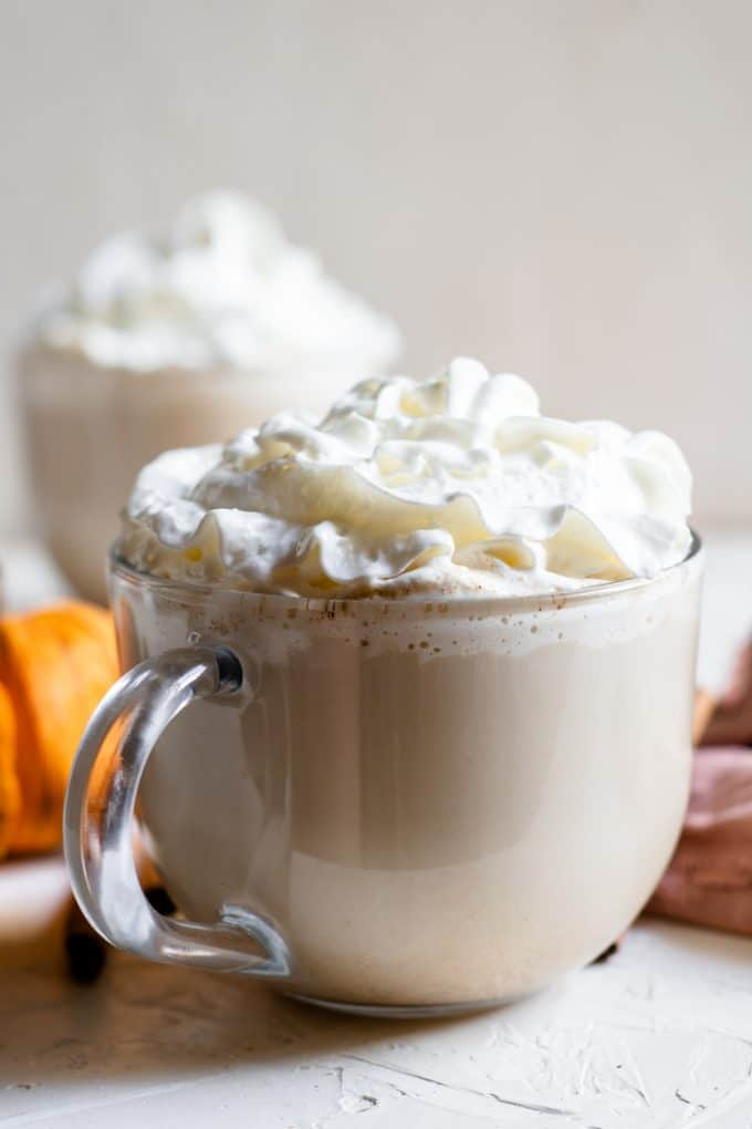 glass mug of pumpkin spice latte with whipped cream