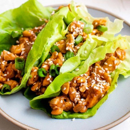 3 lettuce wraps filled with chicken on white plate