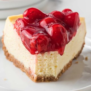 Slice of cheesecake topped with cherry pie filling