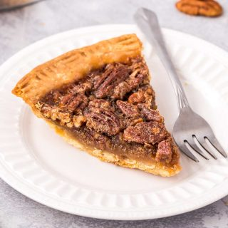 slice of pecan pie on white plate with fork