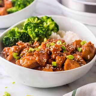 white bowl filled with rice, broccoli and sesame chicken