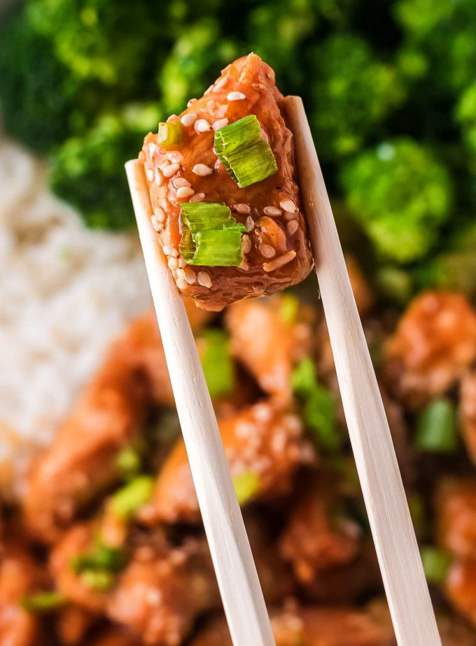 chopsticks holding a piece of chicken with sesame seeds and green onions