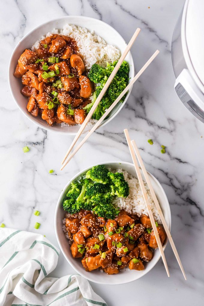 2 bowls with sesame chicken, rice and broccoli with chopsticks