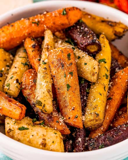 This classic Roasted Carrots recipe combines crisp fresh carrots, seasonings, garlic and Parmesan cheese, and bakes them until tender with lightly caramelized edges!  Savory with a natural sweetness from the carrots, it's the perfect side dish for the holidays or family dinner! #carrots #sidedish #vegetables #roasted #Parmesan #holiday #thanksgiving #easyrecipe #roastedveggies