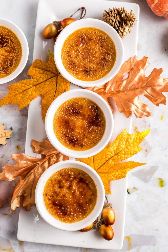 ramekins with creme brulee on platter surrounded by fall leaves