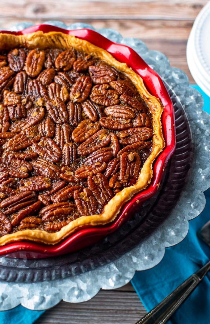 This Bourbon Chocolate Pecan Pie recipe is a fun twist on a classic Fall dessert, and a MUST for any Thanksgiving table. The gooey, sugary center, warm oak-y flavor of the bourbon and decadent dark chocolate, and the crisp nutty top make this the ultimate holiday dessert! #pecanpie #pecan #chocolate #bourbon #thanksgiving #holiday #dessert #baking