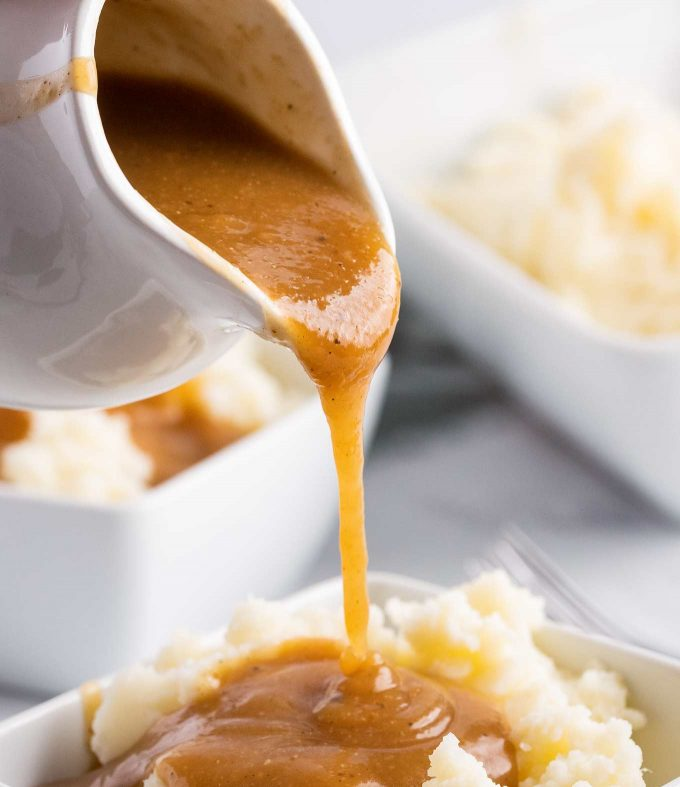 pouring homemade gravy over mashed potatoes