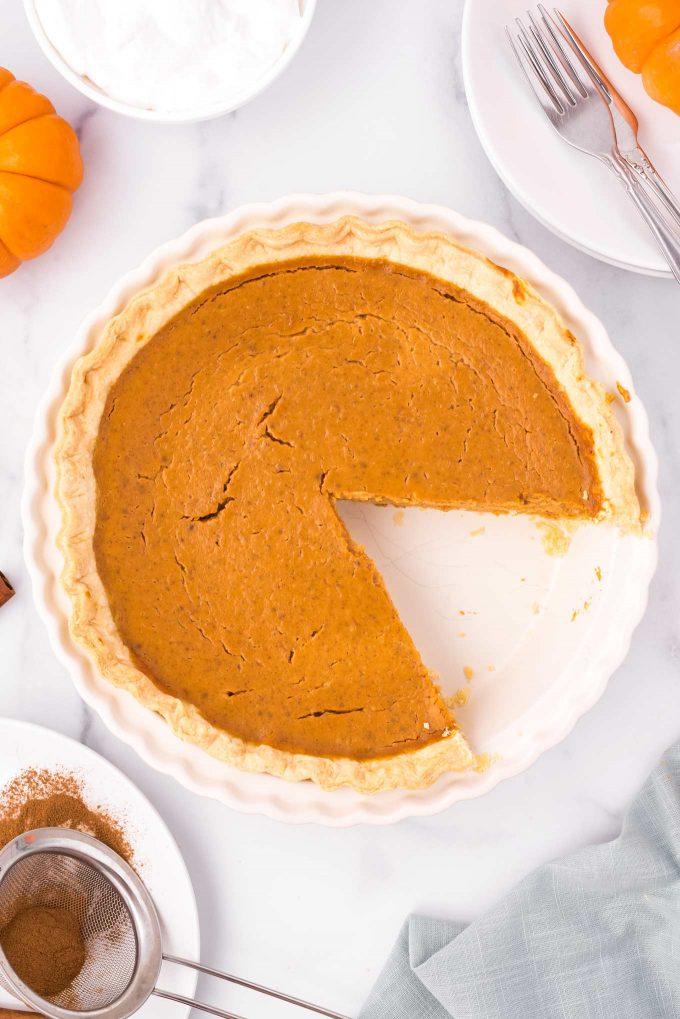 pumpkin pie in pie pan with slice taken out