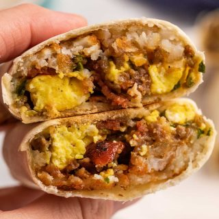 holding a halved breakfast burrito