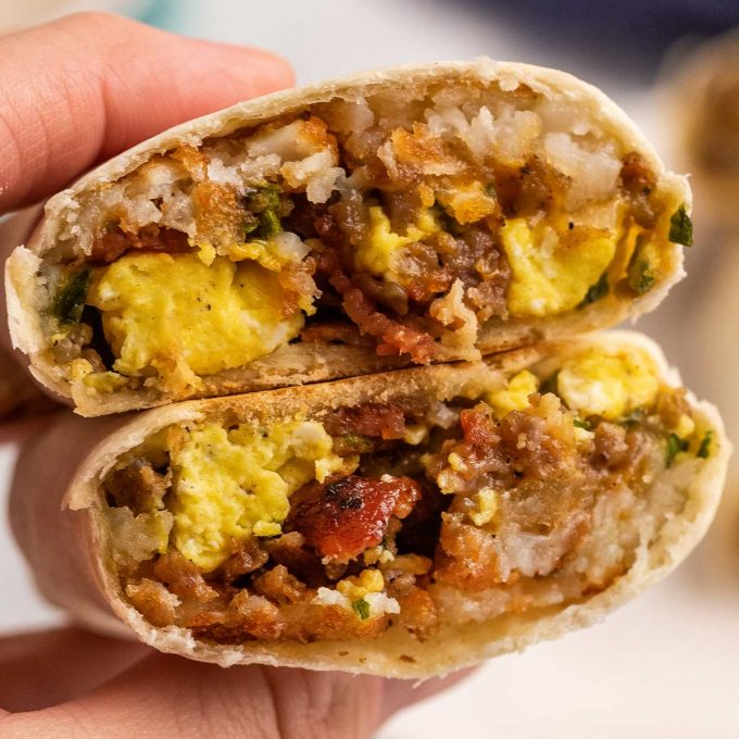 holding a halved breakfast burrito