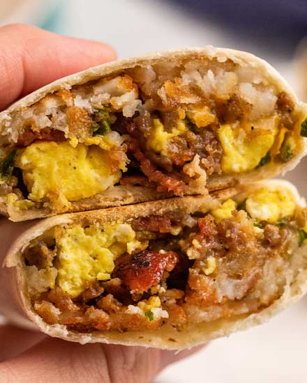 These breakfast burritos are packed with eggs, bacon, sausage, cheese and tater tots and will give you the protein punch you need to get your day started off right!  Easy to prep ahead and freeze, giving you amazing on-the-go burritos all week long! #breakfast #burritos #eggs #bacon #sausage #cheese #hashbrowns #tatertots #freezerfriendly #mealprep