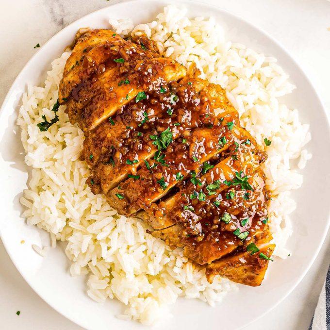 sliced honey garlic chicken breast on top of rice
