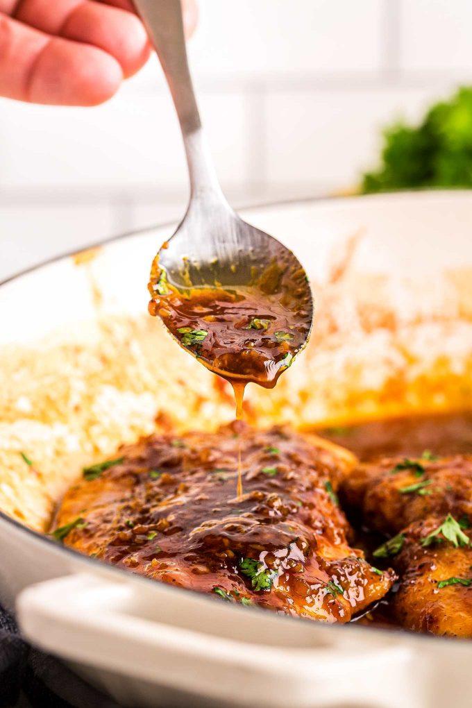 spooning honey garlic sauce over chicken breast in skillet