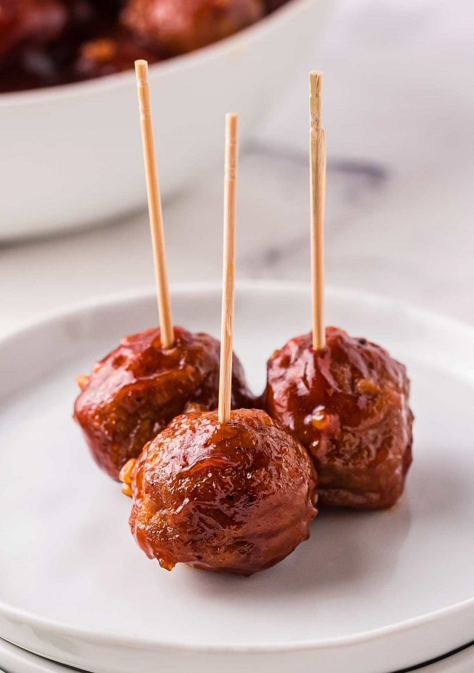 3 meatballs on white plate with toothpicks