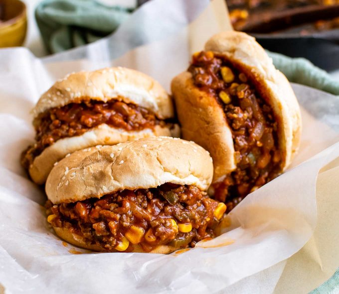 stack of sloppy joe sandwiches on parchment paper