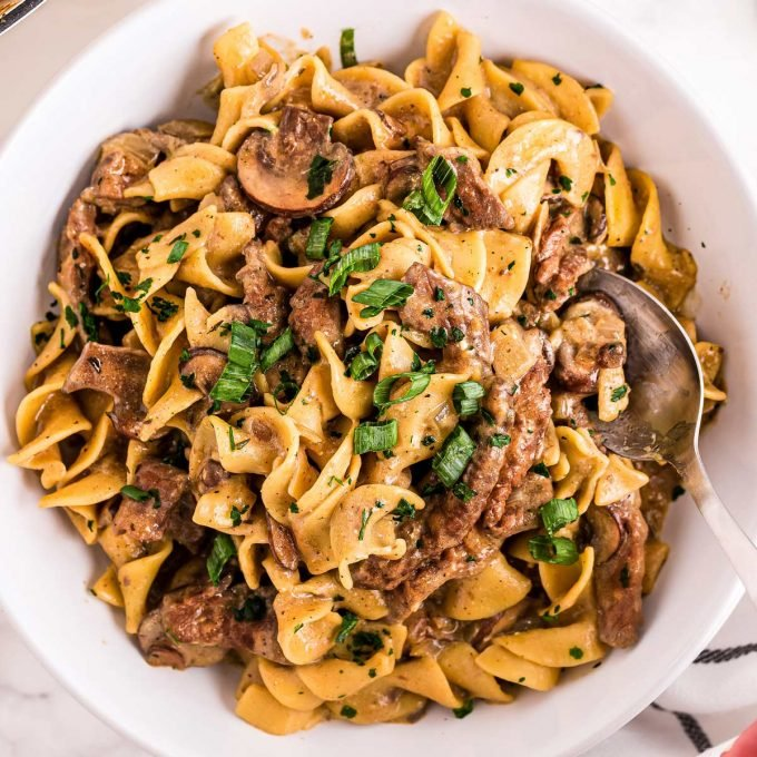 white bowl of beef stroganoff with spoon