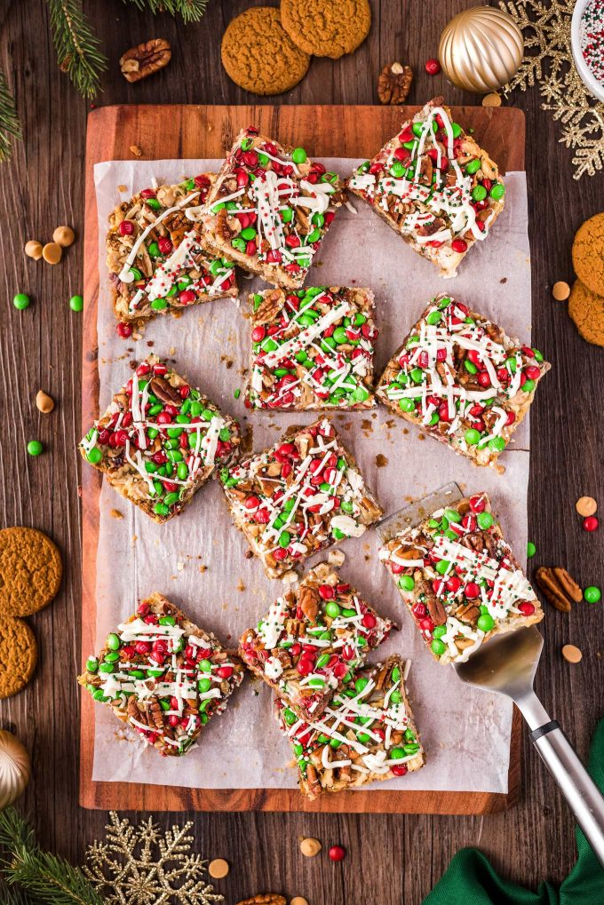 scattered 7 layer bars on holiday cutting board with a spatula