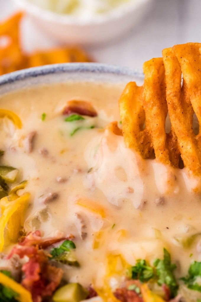 dipping a waffle fry into loaded cheeseburger soup