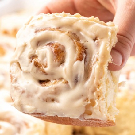holding a cinnamon roll with icing