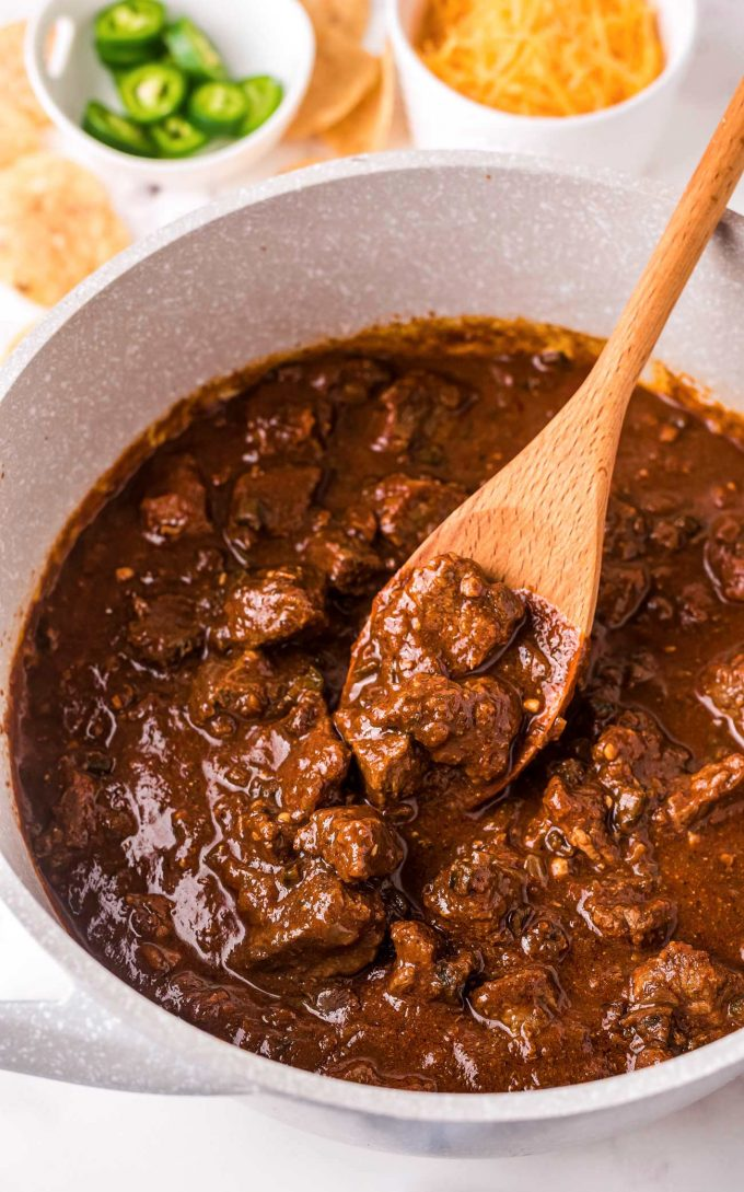 Stirring beef chili with wooden spoon